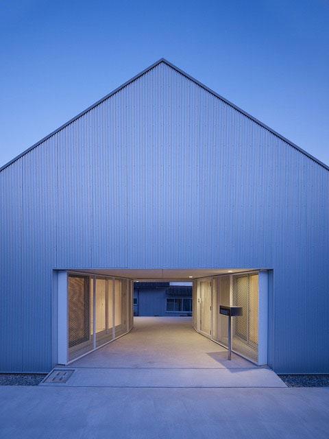 Компактный двухэтажный дом, обшитый серебристым металлическим сайдингом