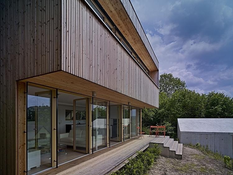 деревянный фасад двухуровневого дома на сложном рельефе
