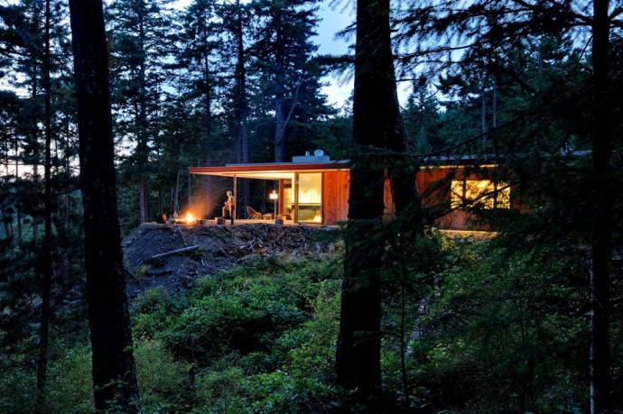 На фото дом с террасой в живописном лесу